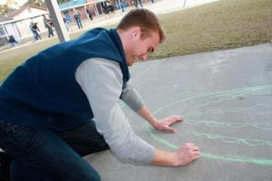 Brandon sketching an outline for a mural. Photo taken from Project Makeover's Facebook